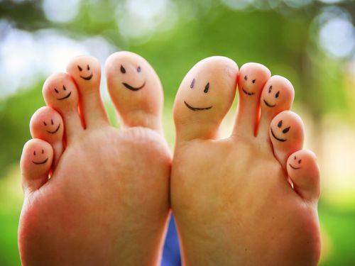 Pieds avec emojis souriants dessinés sur tous les orteils